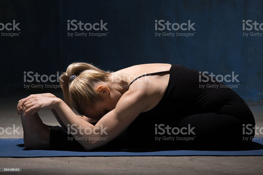 Beautiful Yoga Woman Doing Paschimothanasana Pose stock photo