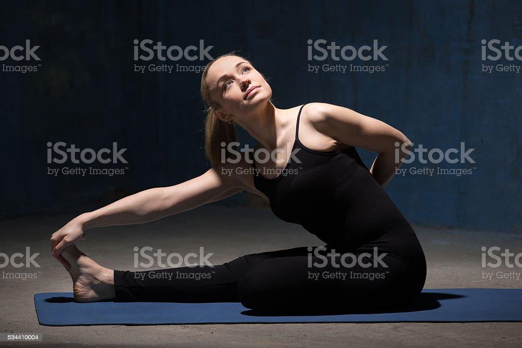 Beautiful Yoga Woman sitting in Half Bound Lotus Forward Bend stock photo