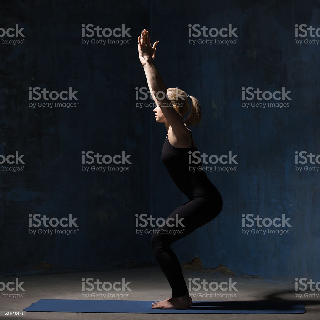 Beautiful Yoga Woman standing in Chair Pose stock photo