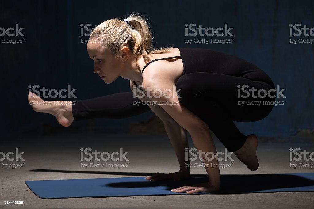 Beautiful Yoga Woman standing in Eka Pada Bakasana 2 stock photo