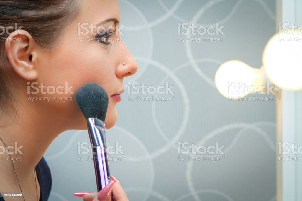 Beautiful young adult woman applying cosmetic paint brush stock photo