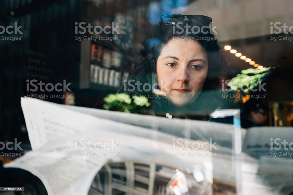Beautiful Young Adult Woman Reading Newspaper stock photo