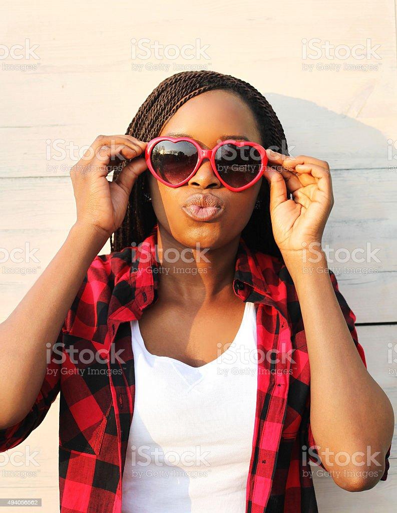 Beautiful young african woman in red sunglasses having fun stock photo