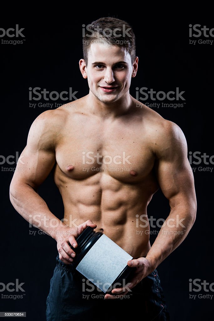 beautiful young athletic man holding a jar of sports nutrition stock photo