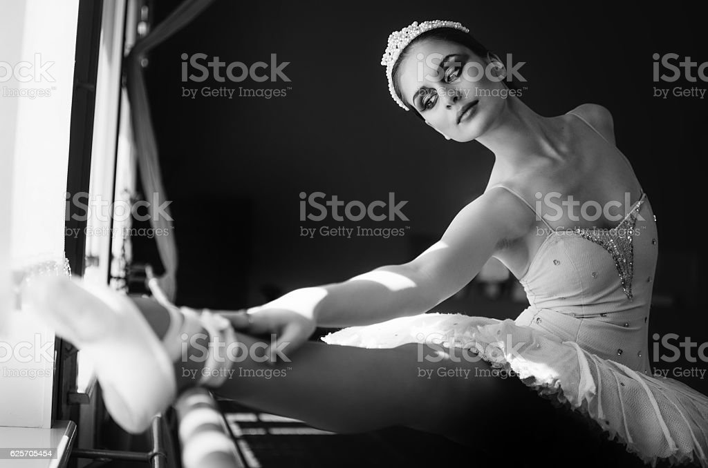 Beautiful young ballerina warming up and stretching trains stock photo