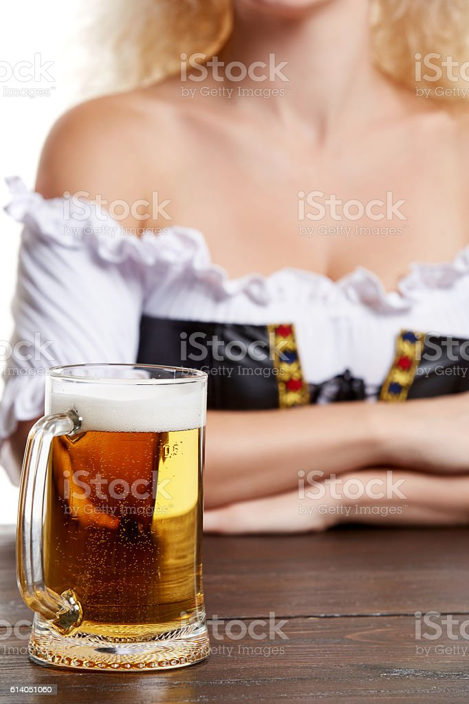 Beautiful young blond girl in traditional costume drinks out of stock photo