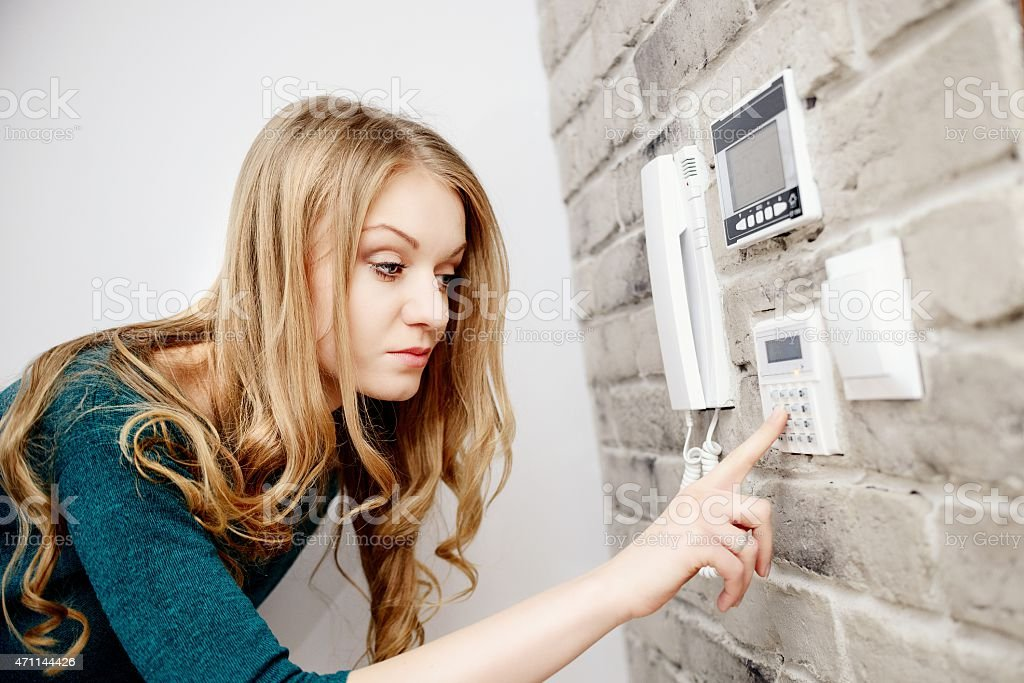 Beautiful young blond woman activates an alarm in the house stock photo