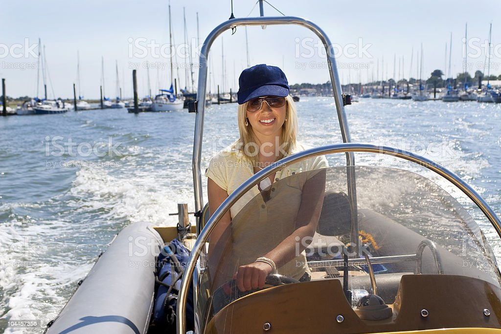 Beautiful Young Blond Woman Driving A Speedboat royalty-free stock photo
