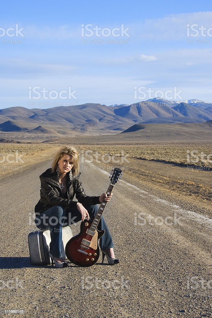 Beautiful young blond woman hitchhicker on the road royalty-free stock photo