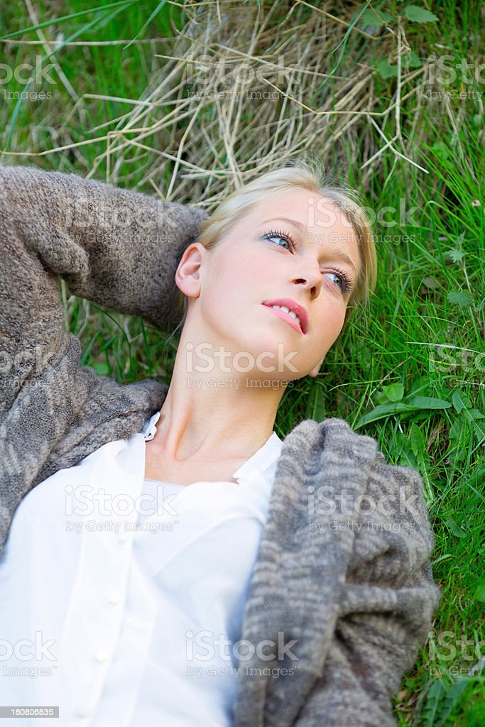Beautiful young blond woman lying in grass royalty-free stock photo