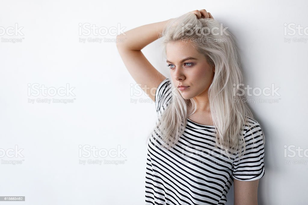 beautiful young blond woman posing while leaning on white wall stock photo