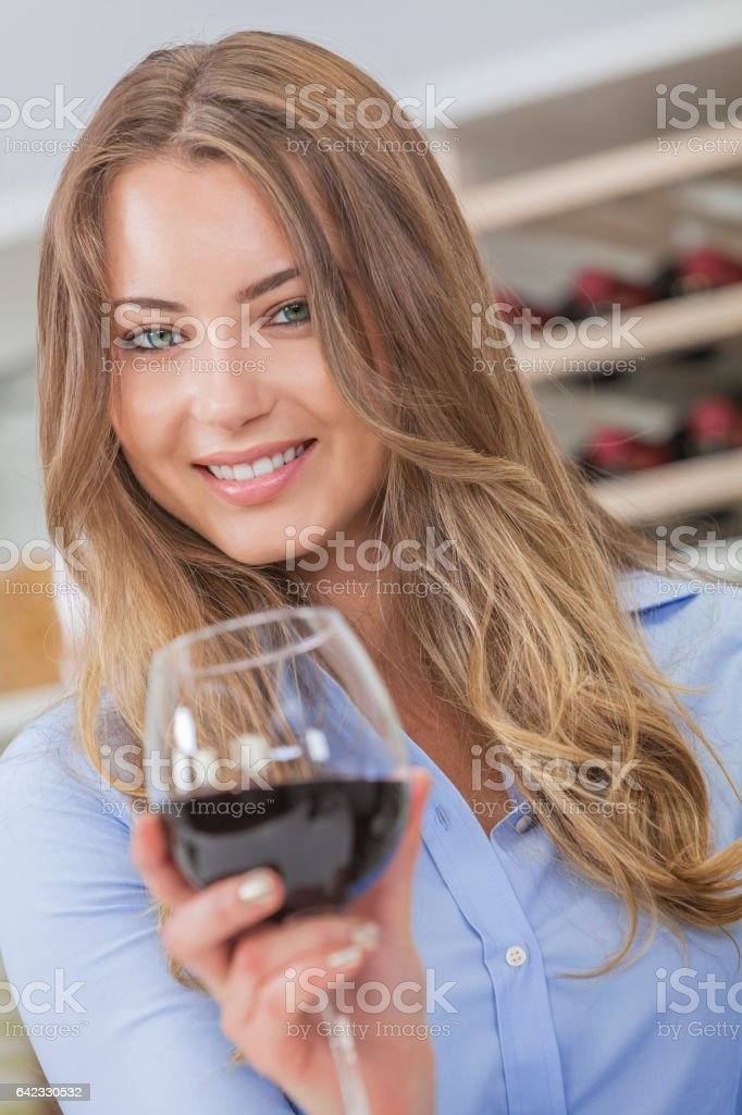 Beautiful young blond woman smiling and drinking a glass of red wine with bottles on a rack behind her stock photo
