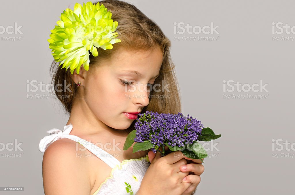 Beautiful young blonde girl smelling flowers. stock photo