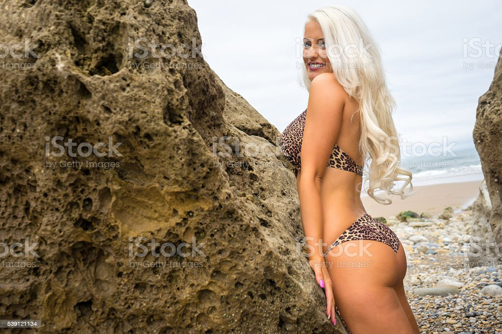 Beautiful young blonde haired woman in bikini stood against rock stock photo