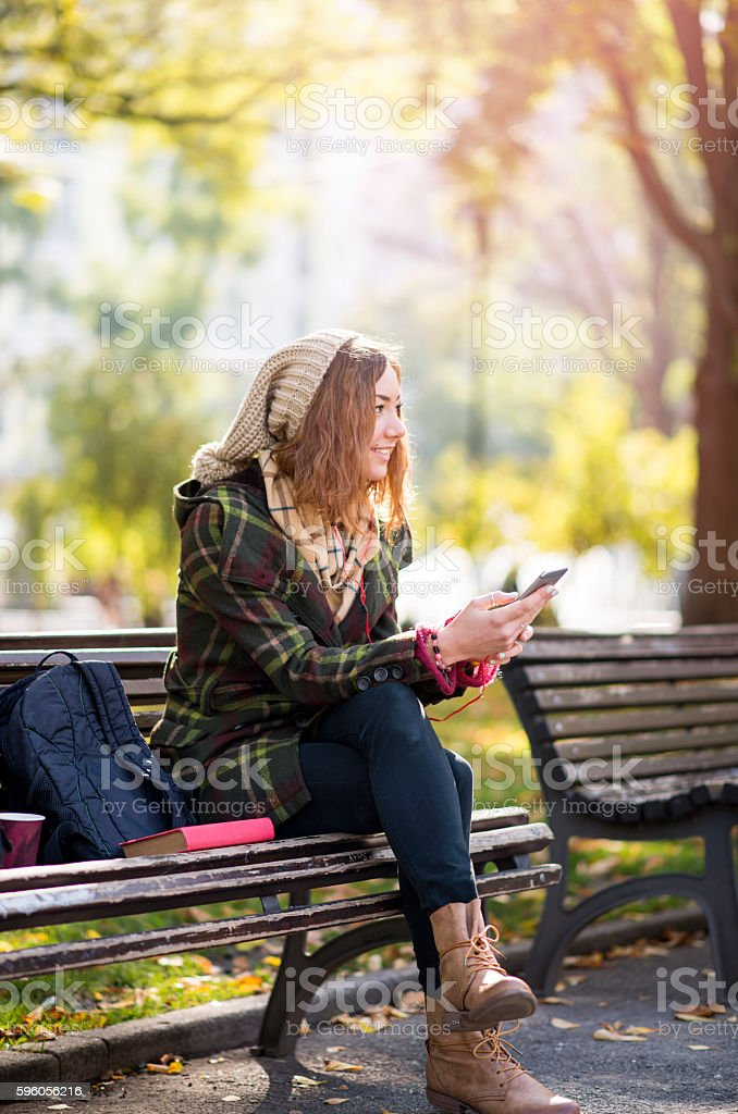 Beautiful young blonde hipster woman listening music stock photo
