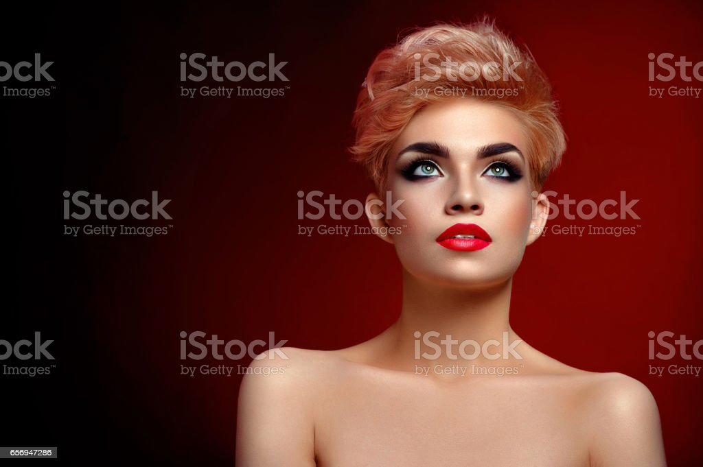 Beautiful young blonde red lipped woman posing in artistic red l stock photo