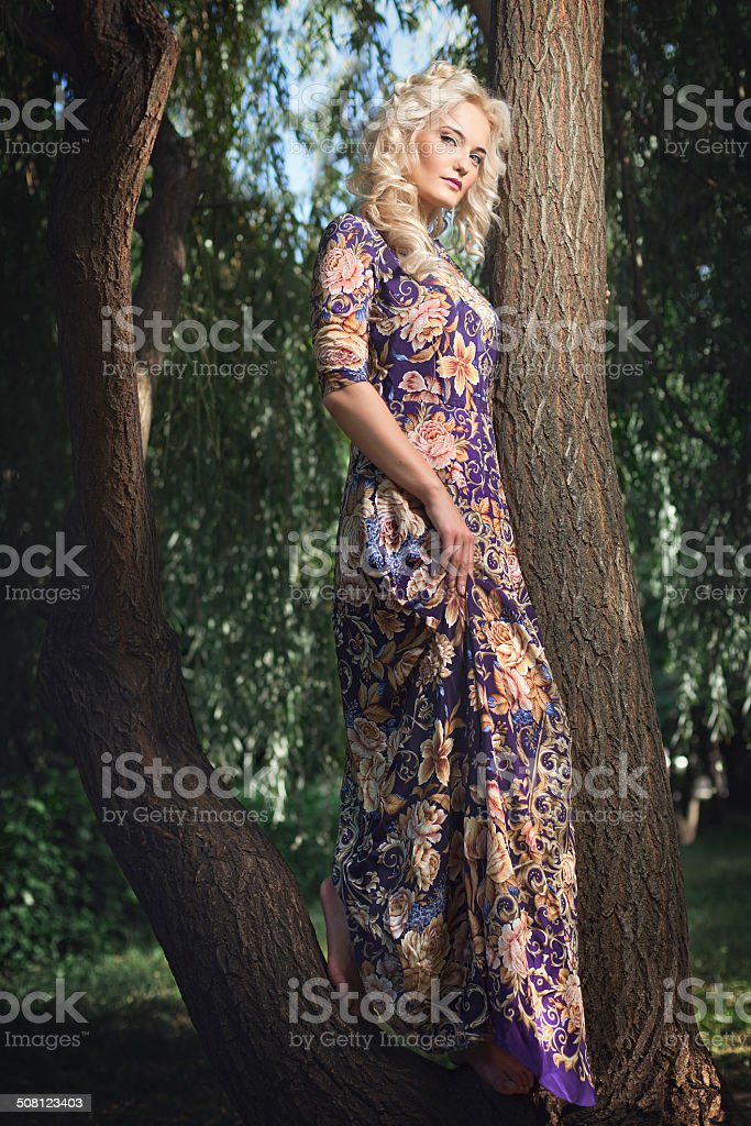 Beautiful young blonde woman walking in the park. stock photo