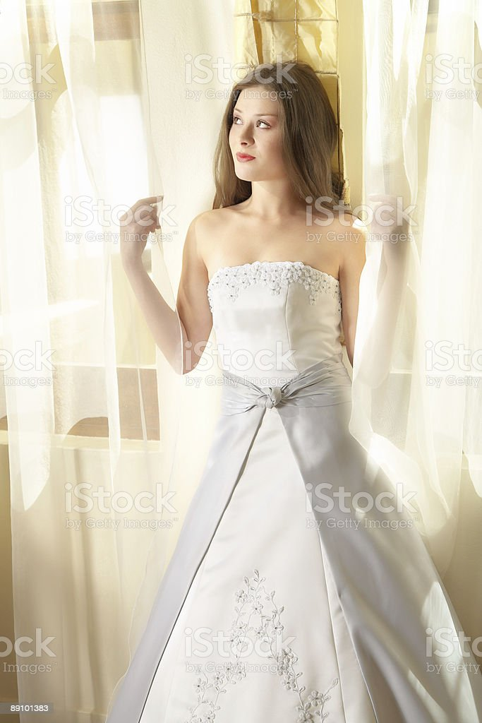 Beautiful young bride at window in natural light royalty-free stock photo