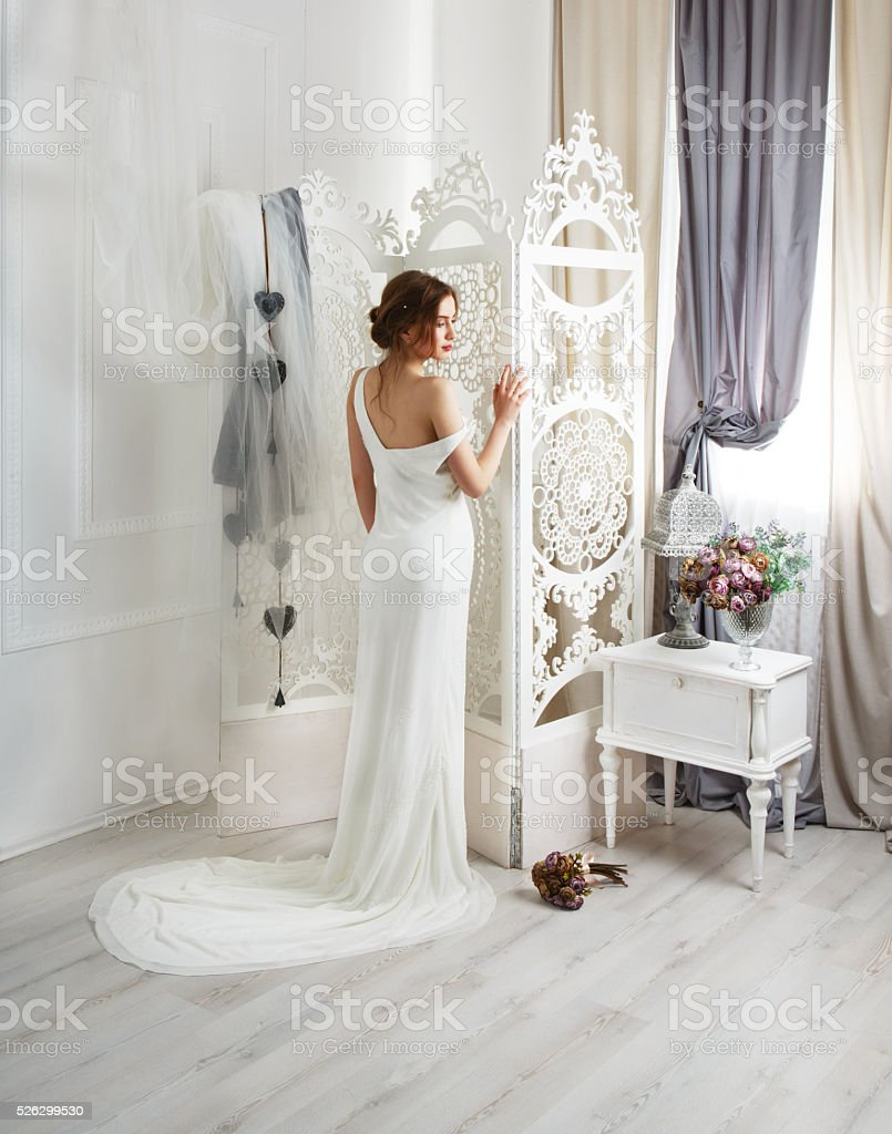 Beautiful young bride in wedding dress with train stock photo