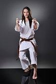 Beautiful young brown belt female karate doing kata