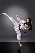 Beautiful young brown belt female karate doing kick