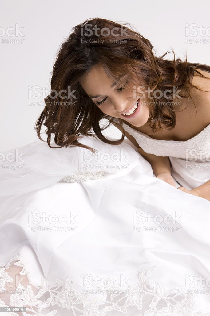 Beautiful Young Brunette Bride Laughing on Floor in Wedding Gown royalty-free stock photo