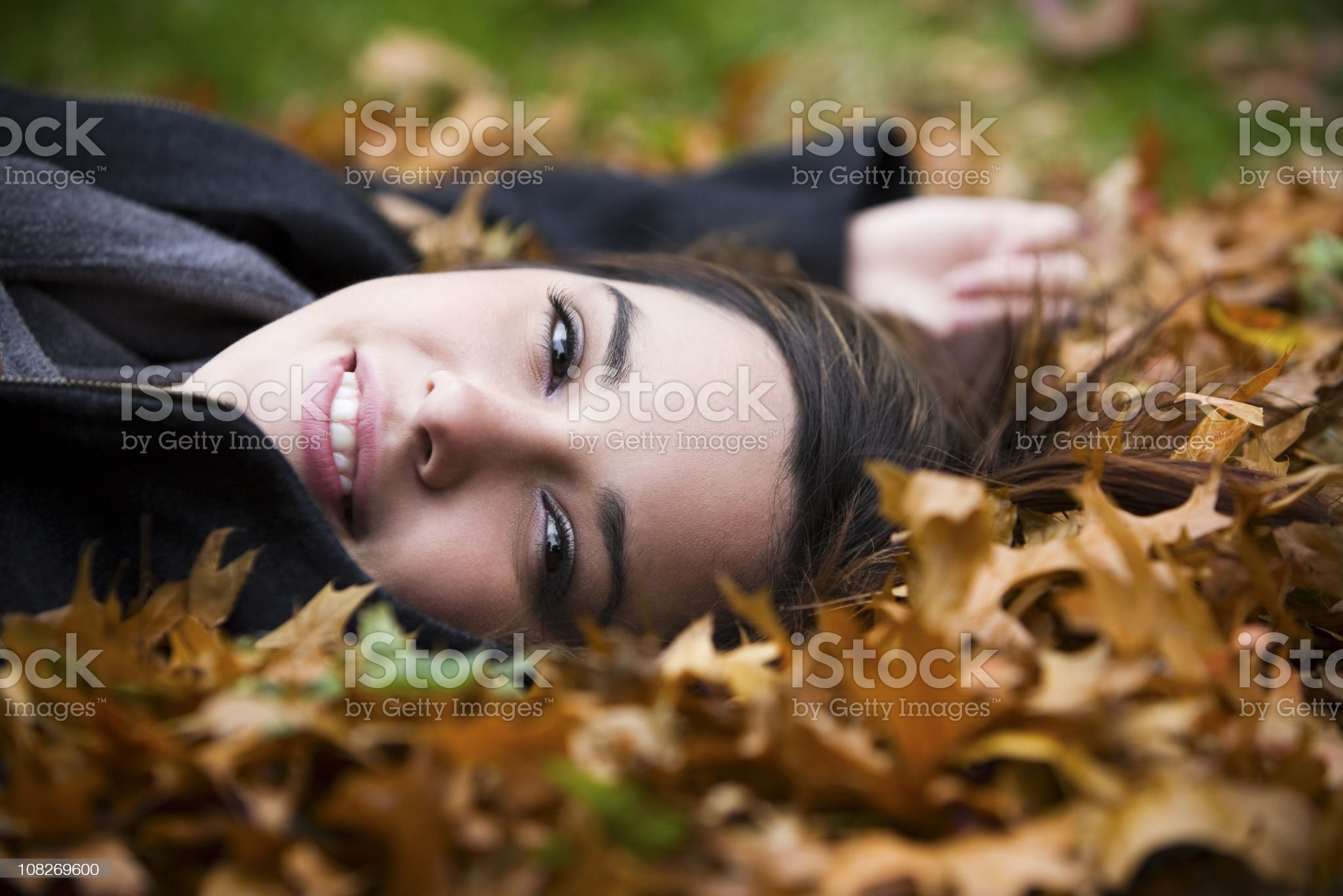 Beautiful Young Brunette Close Up Laying on Fall Leaves, Copyspace royalty-free stock photo