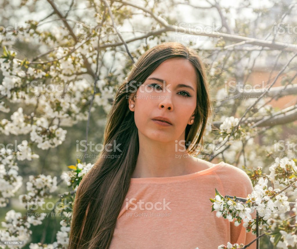 Beautiful young brunette girl in a blooming cherry orchard. Happy smiling young woman with spring flowers at garden. stock photo