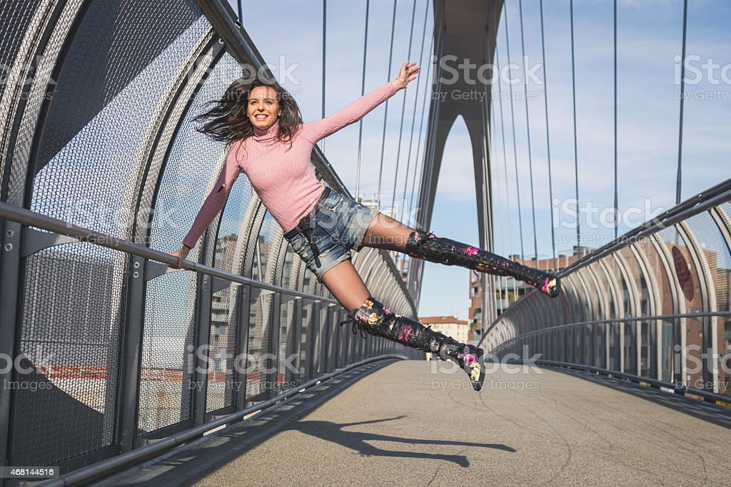 Beautiful young brunette jumping on a bridge stock photo