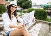 beautiful young brunette looking at map