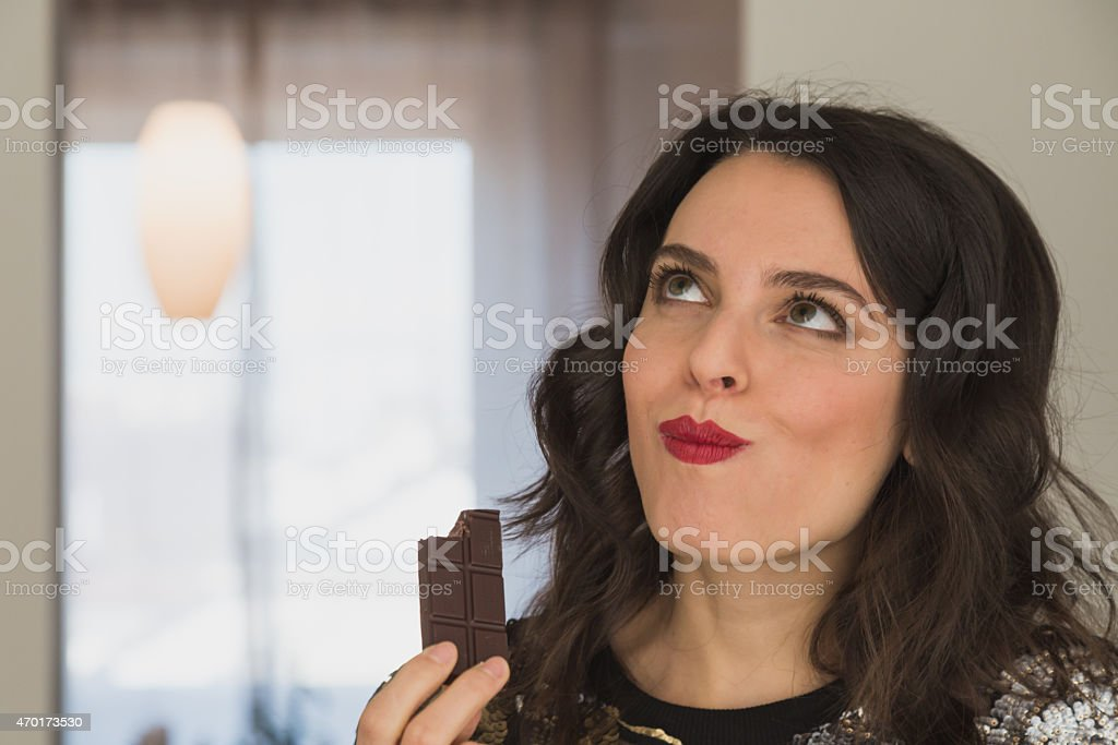 Beautiful young brunette with long hair eating chocolate stock photo