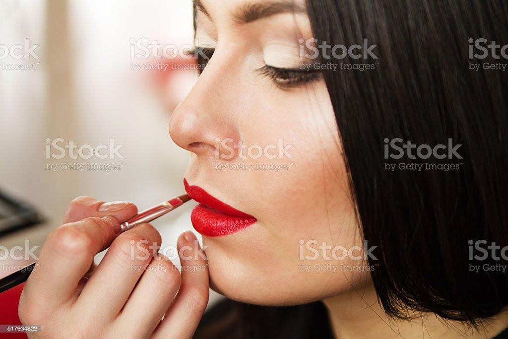 beautiful young brunette woman doing makeup lips. stock photo