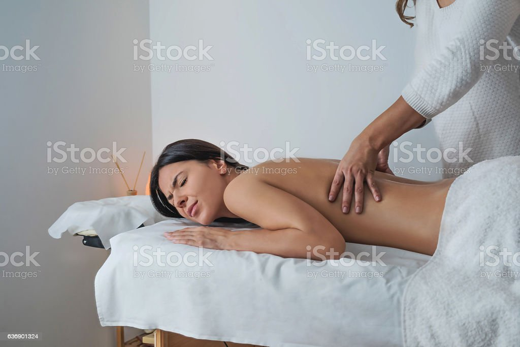 Beautiful young brunette woman experiencing pain during massage stock photo