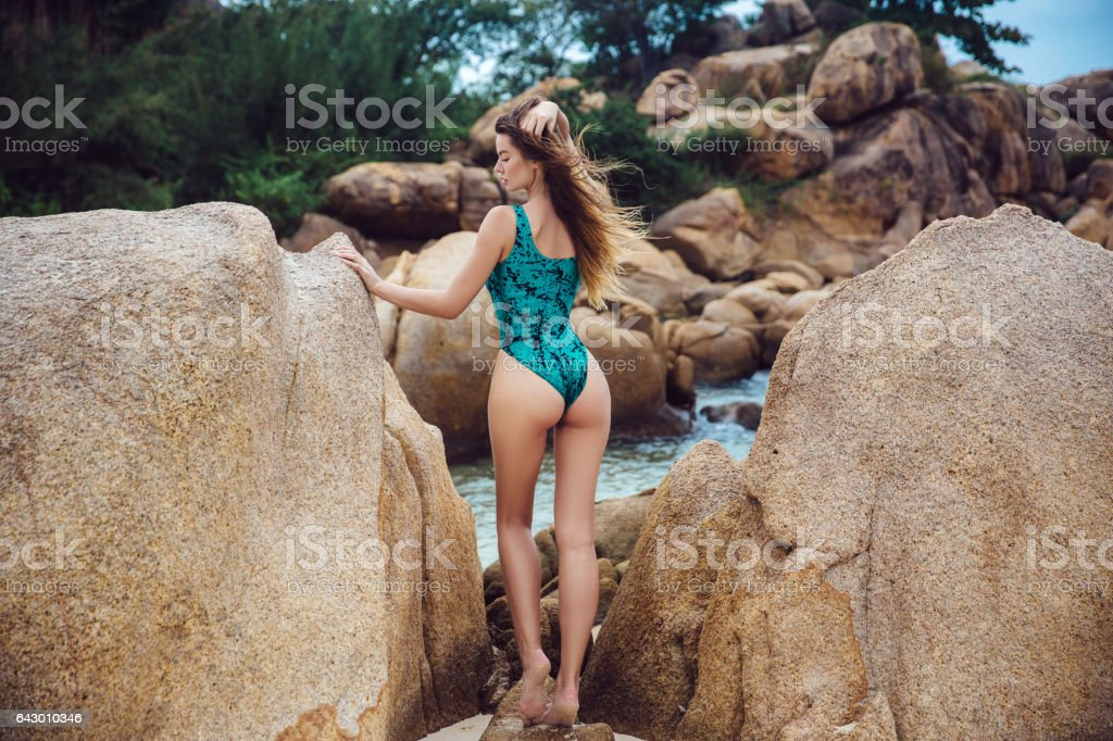 beautiful young brunette woman in blue bikini posing on the beach in turning booty shows ass. Sexy model portrait with perfect body. Concept of summer holidays stock photo
