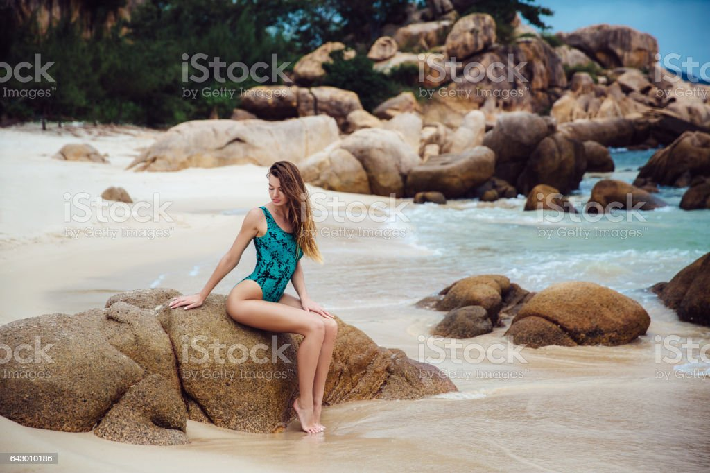beautiful young brunette woman in blue bikini posing on the beach. Sexy model portrait with perfect body. Concept of summer holidays stock photo