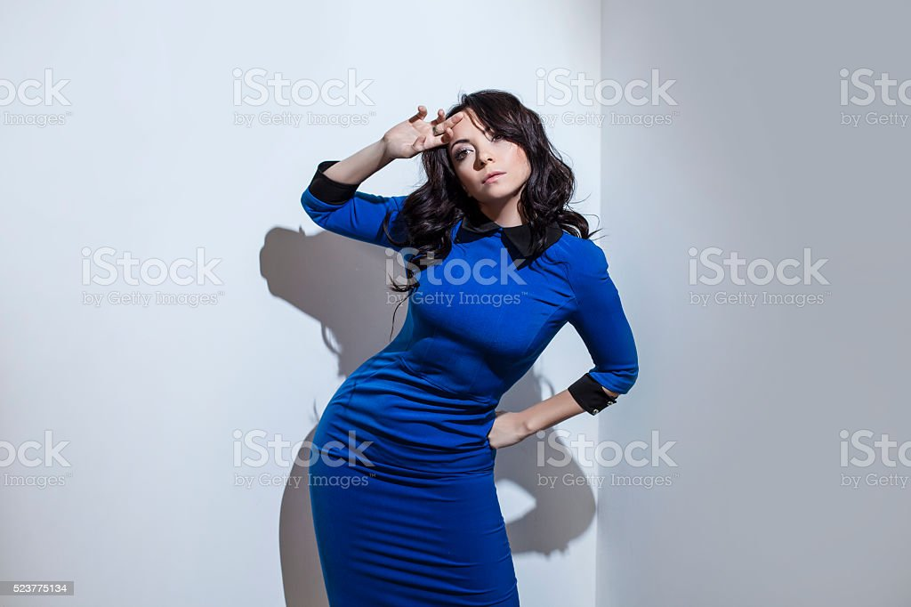 Beautiful young brunette woman in blue dress against stock photo