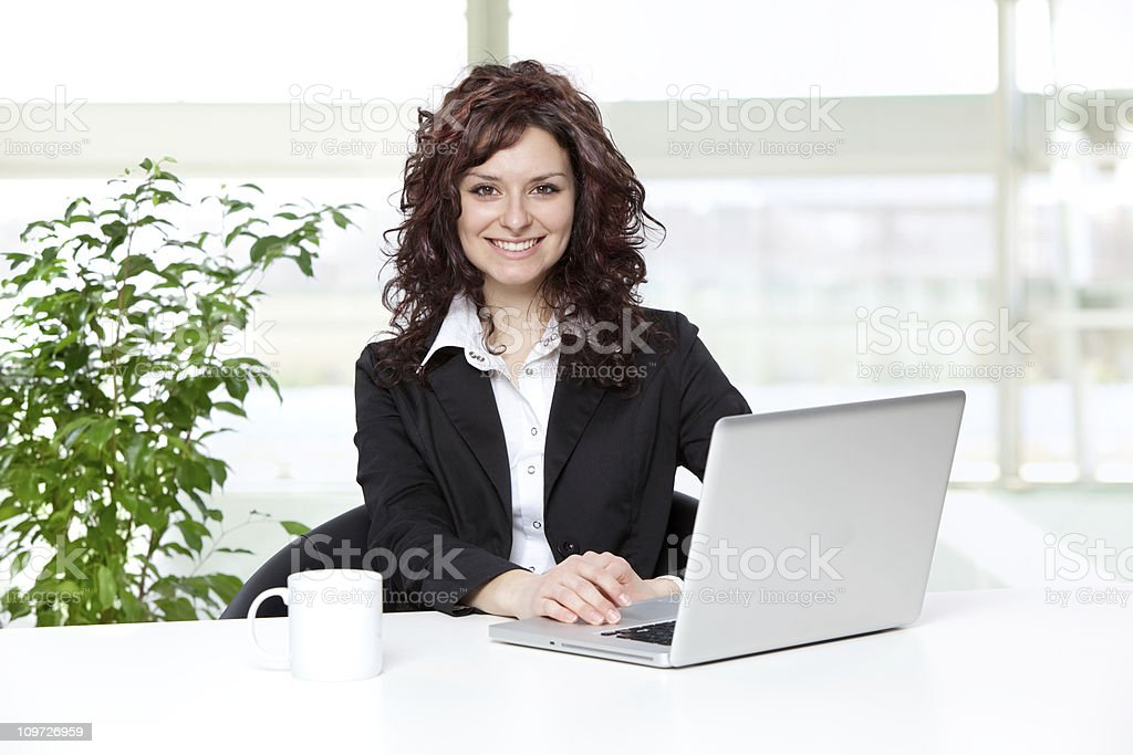 beautiful young buinesswoman portrait at office with laptop and royalty-free stock photo