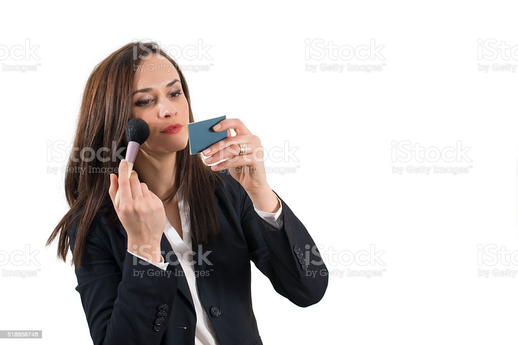 Beautiful young business woman applying her eye makeup stock photo