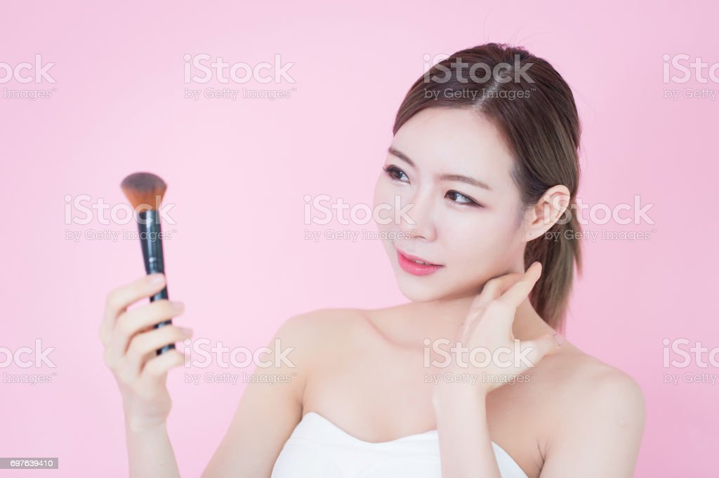 Beautiful young caucasian asian woman smile applying cosmetic brush powder natural makeup. cosmetology, skincare, cleaning face, plastic surgery and SPA therapy concept on pink background stock photo