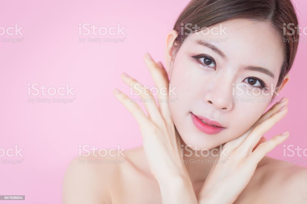 Beautiful young caucasian asian woman touch her clean fresh skin face. cosmetology, skincare, cleaning face, plastic surgery and SPA therapy concept on pink background stock photo