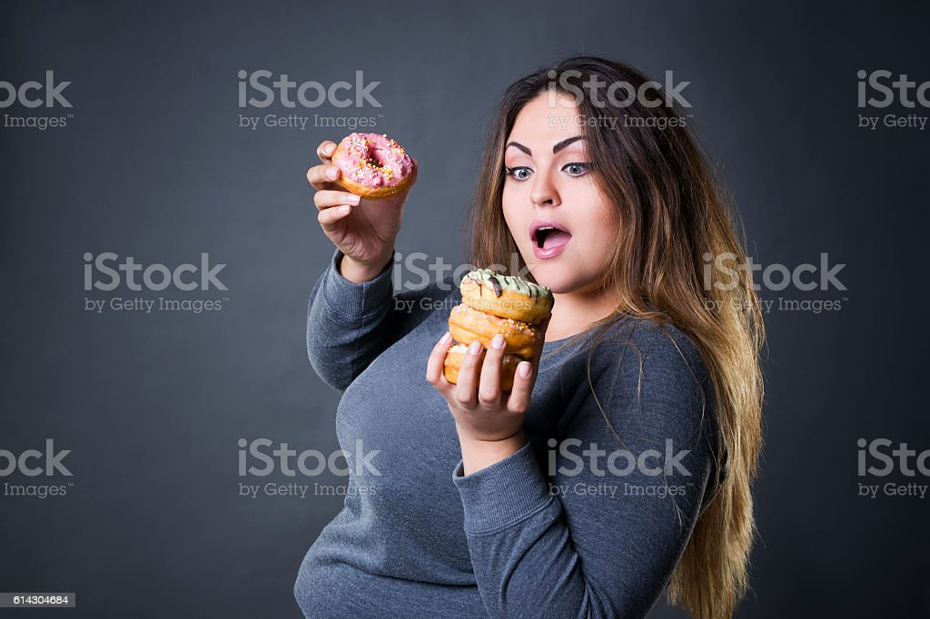 Beautiful young caucasian plus size model posing with donuts stock photo