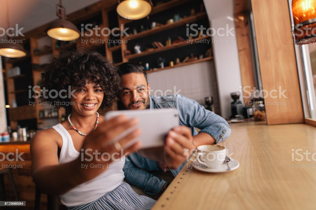 Beautiful young couple at cafe taking selfie with mobile phone stock photo