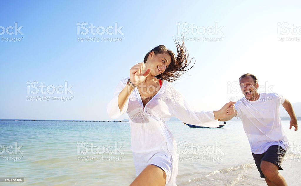 Beautiful young couple chasing at the beach royalty-free stock photo
