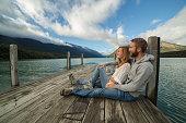 Beautiful young couple cuddling on lake pier-New Zealand