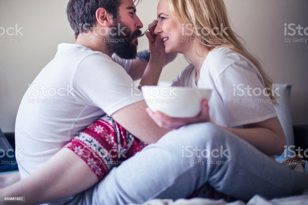 Beautiful young couple having breakfast in bed stock photo