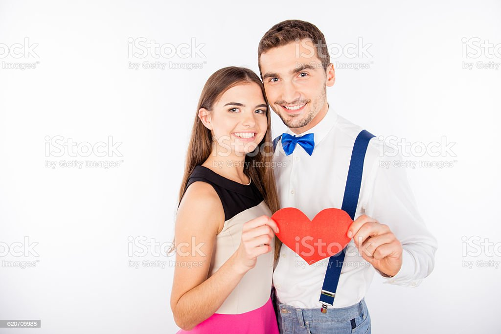 Beautiful young couple holding red paper- heart in their hands stock photo