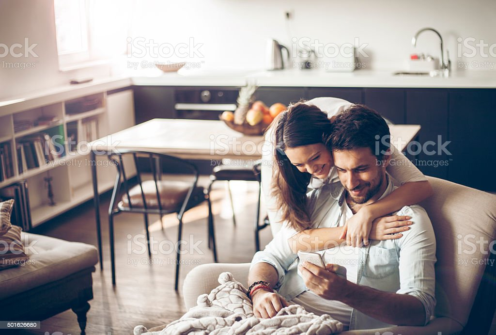 Beautiful young couple looking at smartphone stock photo