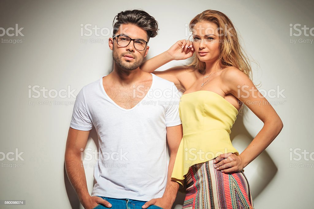 beautiful young couple pose close together looking at the camera stock photo