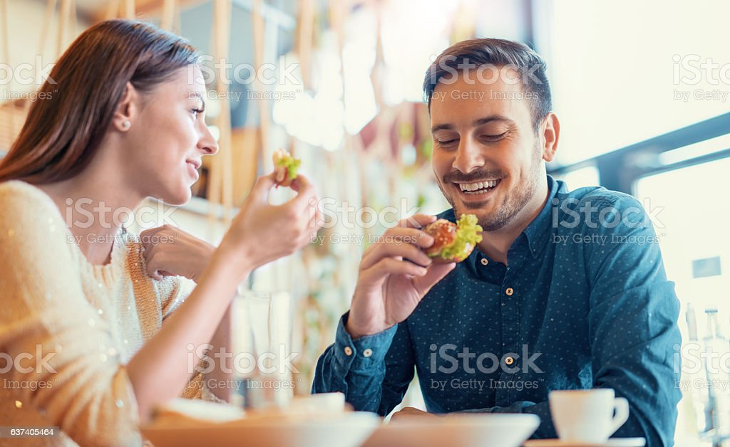 Beautiful young couple sitting in a cafe, having breakfast stock photo