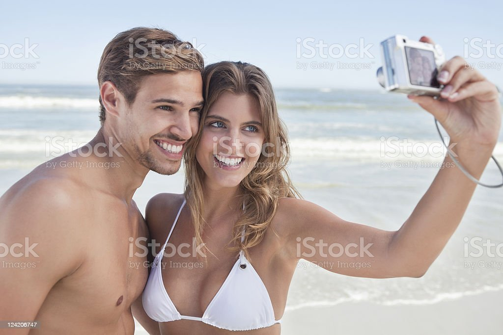 Beautiful young couple taking self portrait on beach royalty-free stock photo